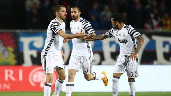 Bonucci y Alves se dan la mano durante un partido de la pasada temporada