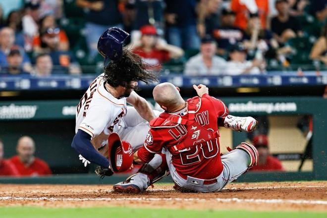 Jake Marisnick # 6 de los Houston Astros choca con el receptor Jonathan Lucroy # 20 de los Angeles Angels of Anaheim cuando intenta anotar en la octava entrada en el Minute Maid Park en Houston, Texas.