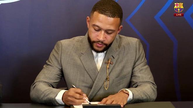 Depay, firmando el contrato con el Barça en su presentación oficial