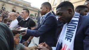 Dembélé (derecha) firma un autógrafo durante las celebraciones en París por la conquista del Mundial de Rusia