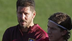 Simeone mirando a Filipe Luís durante un entrenamiento con el Atlético