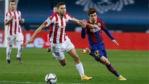 Riqui Puig quiere hacerse con la pelota ante la defensa de Óscar De Marcos en la final de la Supercopa