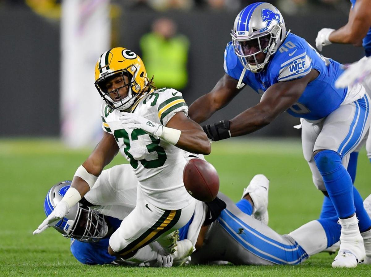 Aaron Jones # 33 de los Green Bay Packers pierde el balón en el primer cuarto contra los Detroit Lions en Lambeau Field.