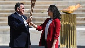 Spyros Capralos, presidente del Comité Olímpico Helénico, entrega la antorcha olímpica a la ex nadadora japonesa Naoko Imoto durante la ceremonia de entrega de la llama olímpica en el Estadio Panatenaico de Atenas