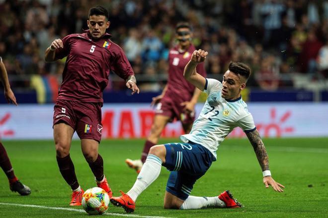 El delantero de la selección de Argentina, Lautaro Martínez (d), disputa el balón ante el centrocampista de Venezuela, Júnior Moreno (i), durante el encuentro amistoso que disputan esta noche en el estadio Wanda Metropolitano, en Madrid.
