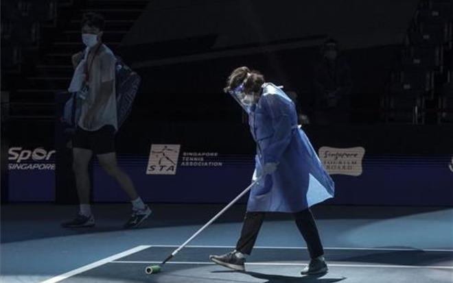 El japonés Taro Daniel pasa junto a un miembro del personal del torneo mientras limpia una cancha del Abierto de Singapur