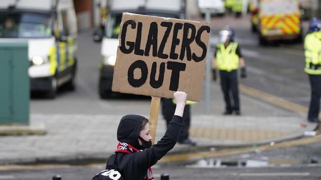Un joven aficionado con una pancarta contra los Glazer