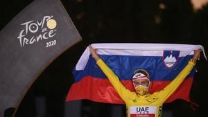Tadej Pogacar sostiene al aire la bandera de Eslovenia en el podio de París