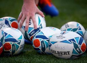 Un jugador recoge una pelota oficial del torneo durante una sesión de entrenamiento del equipo de Gales en Tokio, durante la Copa Mundial de Rugby de Japón 2019.