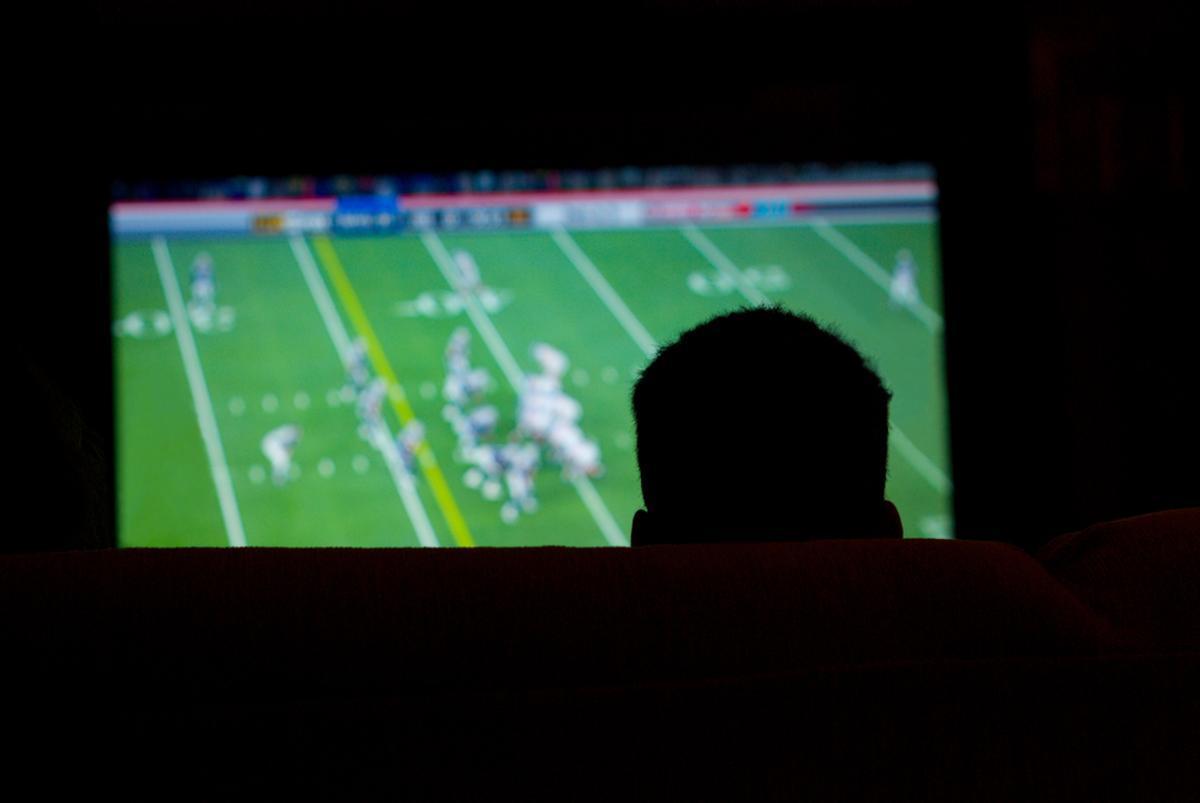 Un hombre ve en la televisión un partido de la NFL.