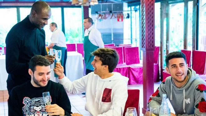 Eric Abidal brinda y conversa de forma animada con Riqui Puig