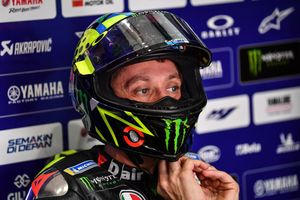 Rossi ajustándose su casco en el box