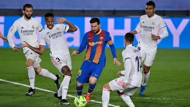Leo Messi envuelto de jugadores del Real Madrid durante el clásico