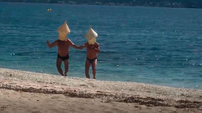 Dos personas se bañan en la playa disfrazados de boya